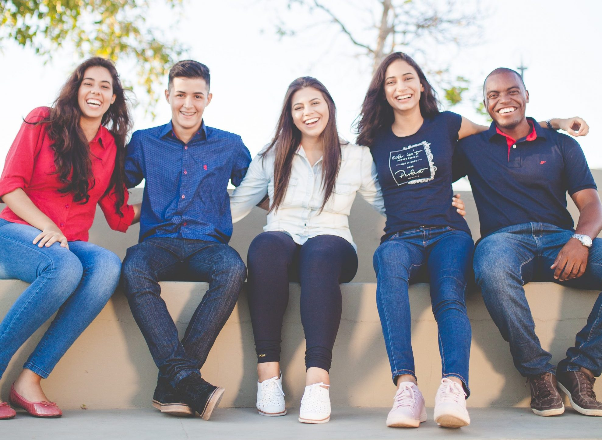 Group of 5 teenagers with arms around each other smiling